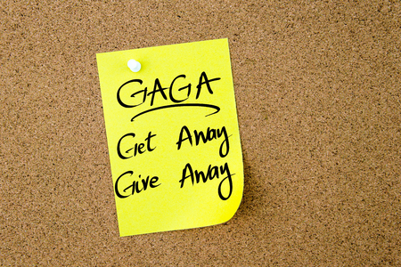 gaga: Business Acronym GAGA Get Away Give Away written on  yellow paper note pinned on cork board with white thumbtack, copy space available
