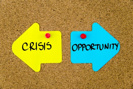 yellow thumbtacks: Message CRISIS versus OPPORTUNITY on yellow and blue paper notes as opposite arrows pinned on cork board with thumbtacks. Choice conceptual image