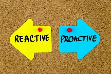 画鋲でコルクボードにピン留め逆矢印として黄色と青の紙のノートにメッセージ プロアクティブと反応。選択の概念図 写真素材