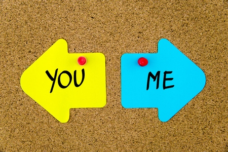 yellow thumbtacks: Message YOU versus ME on yellow and blue paper notes as opposite arrows pinned on cork board with thumbtacks. Choice conceptual image