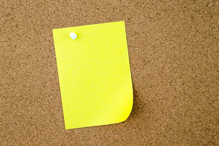 thumbtack: Blank yellow paper note pinned on cork board with white thumbtack, copy space available