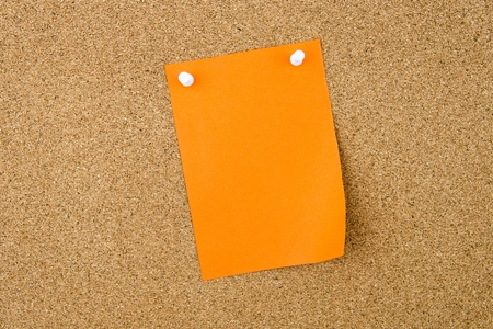 cork sheet: Blank orange paper note pinned on cork board with white thumbtacks, copy space available