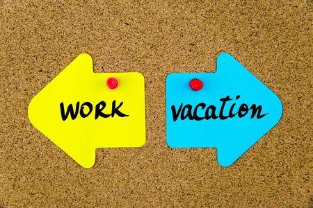 yellow thumbtacks: Message WORK versus VACATION on yellow and blue paper notes as opposite arrows pinned on cork board with thumbtacks. Choice conceptual image