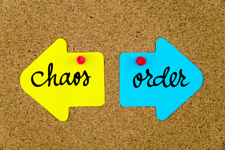 chaos order: Message CHAOS versus ORDER on yellow and blue paper notes as opposite arrows pinned on cork board with thumbtacks. Choice conceptual image Stock Photo