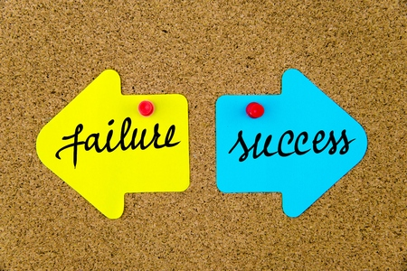 yellow thumbtacks: Message FAILURE versus SUCCESS on yellow and blue paper notes as opposite arrows pinned on cork board with thumbtacks. Choice conceptual image Stock Photo