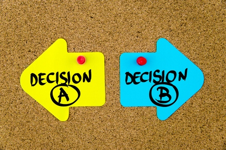 yellow thumbtacks: Message DECISION A versus DECISION B on yellow and blue paper notes as opposite arrows pinned on cork board with thumbtacks. Choice conceptual image