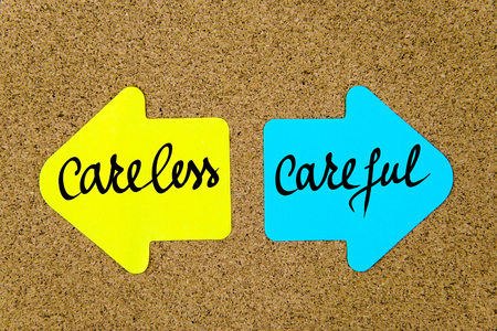 careful: Message Careless versus Careful on yellow and blue paper notes as opposite arrows pinned on cork board with thumbtacks. Choice conceptual image Stock Photo