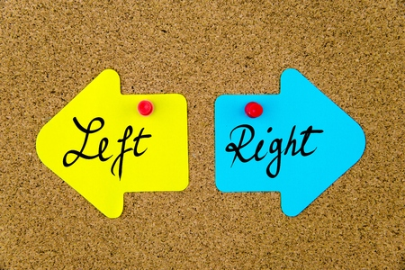 yellow thumbtacks: Message LEFT versus RIGHT on yellow and blue paper notes as opposite arrows pinned on cork board with thumbtacks. Choice conceptual image
