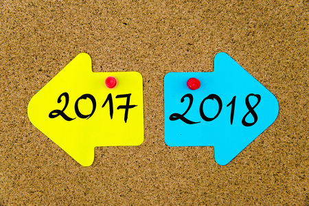 yellow thumbtacks: Message 2017 versus 2018 on yellow and blue paper notes as opposite arrows pinned on cork board with thumbtacks. Choice conceptual image Stock Photo