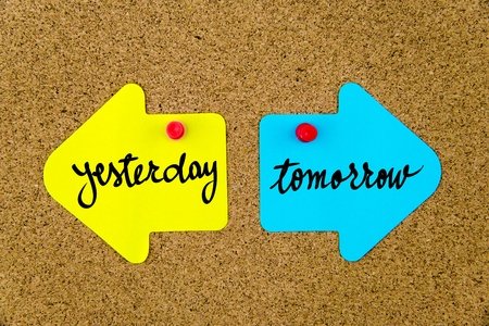 yellow thumbtacks: Message YESTERDAY versus TOMORROW on yellow and blue paper notes as opposite arrows pinned on cork board with thumbtacks. Choice conceptual image Stock Photo