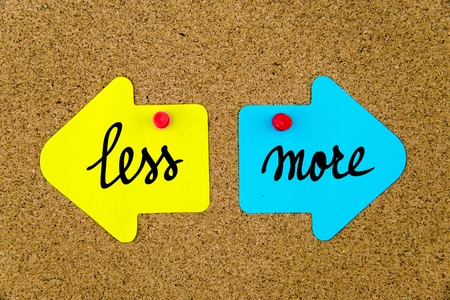 yellow thumbtacks: Message LESS versus MORE on yellow and blue paper notes as opposite arrows pinned on cork board with thumbtacks. Choice conceptual image Stock Photo