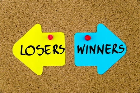 yellow thumbtacks: Message LOSERS versus WINNERS on yellow and blue paper notes as opposite arrows pinned on cork board with thumbtacks. Choice conceptual image Stock Photo