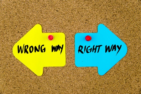 yellow thumbtacks: Message WRONG WAY versus RIGHT WAY on yellow and blue paper notes as opposite arrows pinned on cork board with thumbtacks. Choice conceptual image