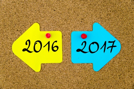 yellow thumbtacks: Message 2016 versus 2017 on yellow and blue paper notes as opposite arrows pinned on cork board with thumbtacks. Choice conceptual image