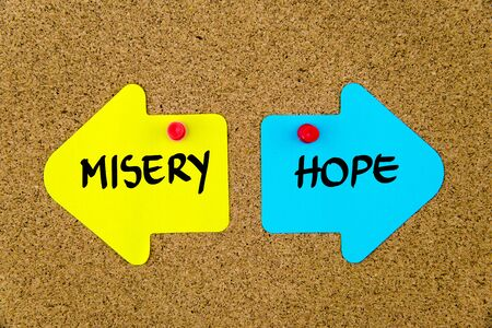 misery: Message MISERY versus HOPE on yellow and blue paper notes as opposite arrows pinned on cork board with thumbtacks. Choice conceptual image