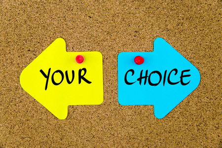 yellow thumbtacks: Message YOUR CHOICE on yellow and blue paper notes as opposite arrows pinned on cork board with thumbtacks. Choice conceptual image