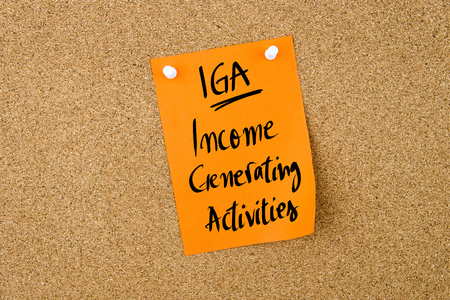iga: Business Acronym IGA Income Generating Activities written on  yellow paper note pinned on cork board with white thumbtack, copy space available Stock Photo