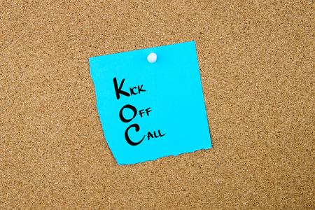 kick off: Business Acronym KOC Kick Off Call written on blue paper note pinned on cork board with white thumbtack, copy space available