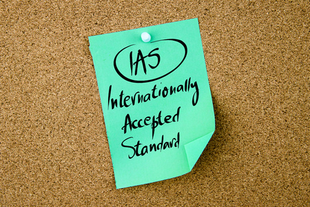 internationally: Business Acronym IAS Internationally Accepted Standard written on green paper note pinned on cork board with white thumbtack, copy space available Stock Photo