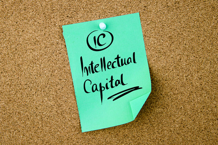 Ic: Business Acronym IC Intellectual Capital written on green paper note pinned on cork board with white thumbtack, copy space available