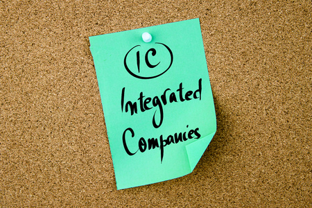 Ic: Business Acronym IC Integrated Companies written on green paper note pinned on cork board with white thumbtack, copy space available Stock Photo