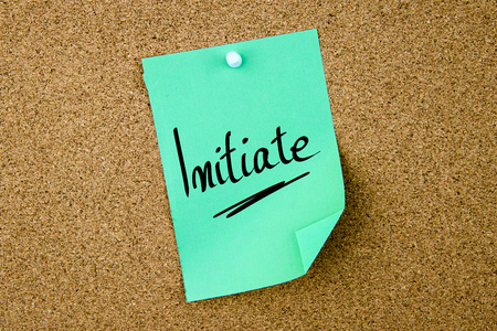 initiate: Initiate written on green paper note pinned on cork board with white thumbtacks, copy space available Stock Photo
