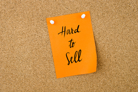 hard sell: Hard To Sell written on orange paper note pinned on cork board with white thumbtacks, copy space available