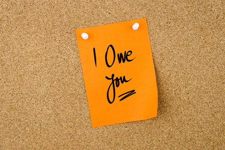 I Owe You written on orange paper note pinned on cork board with white thumbtacks, copy space available