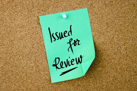 issued: Issued For Review written on green paper note pinned on cork board with white thumbtacks, copy space available Stock Photo