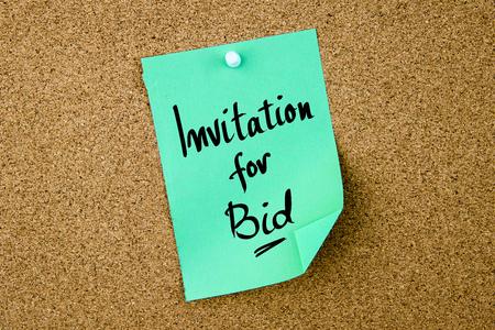 bid: Llamado a Licitación nota escrita en papel verde depositado en el tablón de corcho con chinchetas blanco, copia espacio disponible