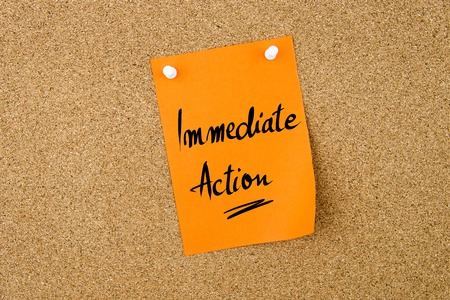 immediate: Immediate Action written on orange paper note pinned on cork board with white thumbtacks, copy space available
