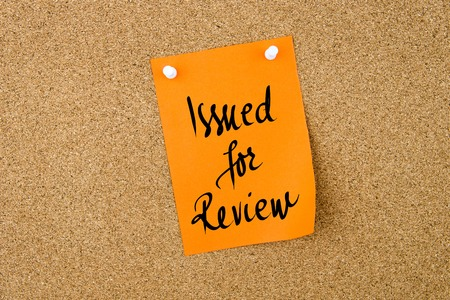 issued: Issued For Review written on orange paper note pinned on cork board with white thumbtacks, copy space available Stock Photo