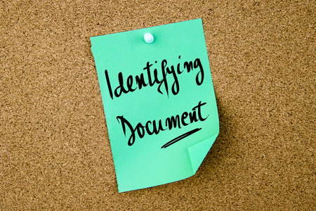 identifying: Identifying Document written on green paper note pinned on cork board with white thumbtacks, copy space available Stock Photo