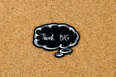 big cork: Think BIG written on black thinking bubble over cork board background, copy space available