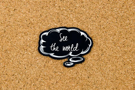 world thinking: SEE THE WORLD written on black thinking bubble over cork board background, copy space available