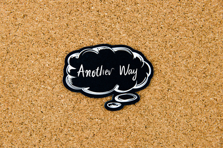 another way: Another Way written on black thinking bubble over cork board background, copy space available