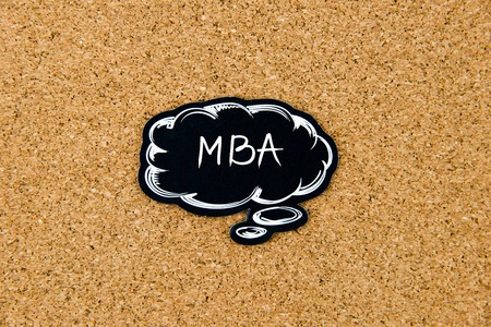 marking up: MBA written on black thinking bubble over cork board background, copy space available