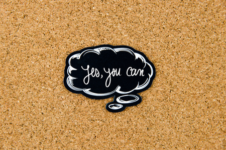 thinking of you: YES, YOU CAN written on black thinking bubble over cork board background, copy space available