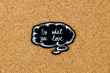 thinking of you: DO WHAT YOU LOVE written on black thinking bubble over cork board background, copy space available Stock Photo