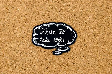 thinking bubble: DARE TO TAKE RISKS written on black thinking bubble over cork board background, copy space available