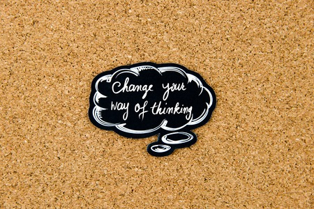 way of thinking: Change Your Way Of Thinking written on black thinking bubble over cork board background, copy space available