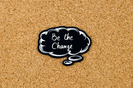marking up: Be The Change written on black thinking bubble over cork board background, copy space available