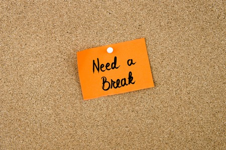in need of space: Need A Break written on orange paper note pinned on cork board with white thumbtacks, copy space available