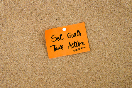 take a note: Set Goals Take Action written on orange paper note pinned on cork board with white thumbtacks, copy space available
