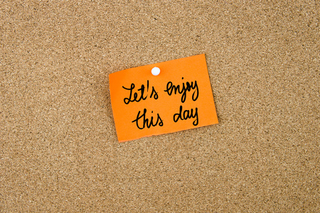 enjoy space: Lets Enjoy This Day written on orange paper note pinned on cork board with white thumbtacks, copy space available