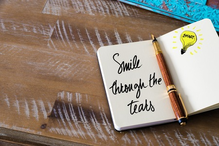 follow through: Handwritten text Smile Through The Tears with fountain pen on notebook. Concept image with copy space available. Stock Photo