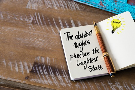 brightest: Handwritten text The darkest nights produce the brightest stars with fountain pen on notebook. Concept image with copy space available.