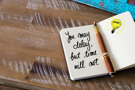 delay: Handwritten text You May delay, But Time Will Not with fountain pen on notebook. Concept image with copy space available.
