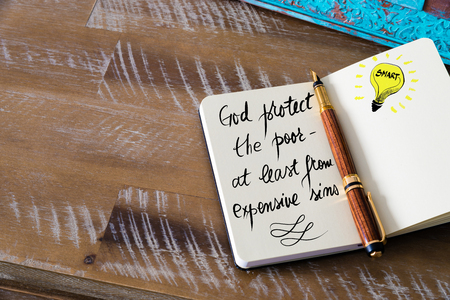 sins: Handwritten text God protect the poor � at least from expensive sins with fountain pen on notebook. Concept image with copy space available.
