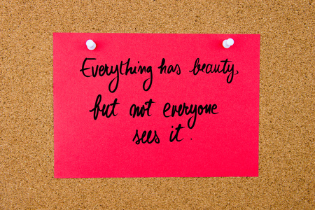 sees: Red paper note with handwritten text Everything Has Beauty, But Not Everyone Sees It pinned on cork board with white thumbtacks